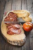 picture of charcuterie  - Morcon a Spanish sausage like chorizo with bread and tomato on the cutting board - JPG