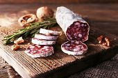 foto of sackcloth  - French salami on cutting board on sackcloth napkin on wooden background - JPG