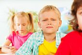 pic of frown  - Frowning boy looking straight in classroom of the school between other pupils sitting at desk - JPG