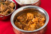 image of kadai  - Chili garlic chicken in a serving bowl with rice and chicken malabar behind - JPG