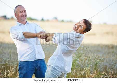 Smiling senior couple dancing in summer in a wheat field