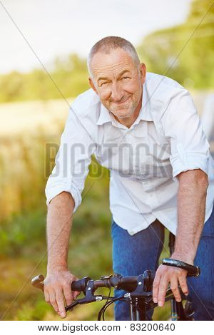 Smiling old man riding bike in summer in nature