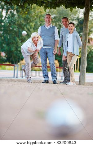 Woman throwing ball while playing boule game with senior people