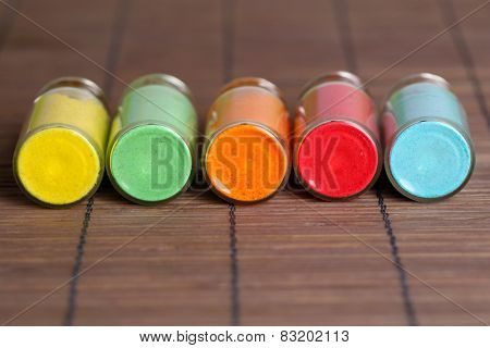 Bottles with colorful dry pigments on bamboo mat background