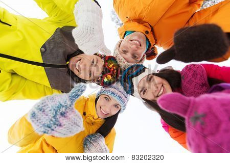 winter, leisure, friendship and people concept - happy friends standing in circle outdoors, showing thumbs up and and looking down