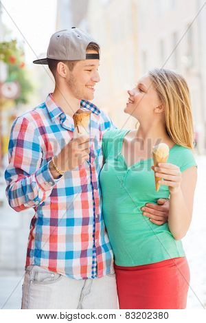summer, vacation, love and friendship concept - smiling couple with ice-cream looking to each other in city