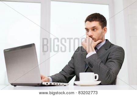 business, people, technology and work concept - businessman sitting in front of laptop and typing in office