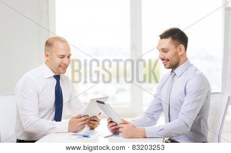 business, technology and office concept - two smiling businessmen with tablet pc computers and files in office
