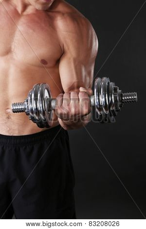 Muscle young sportsman execute exercise with dumbbell on dark background