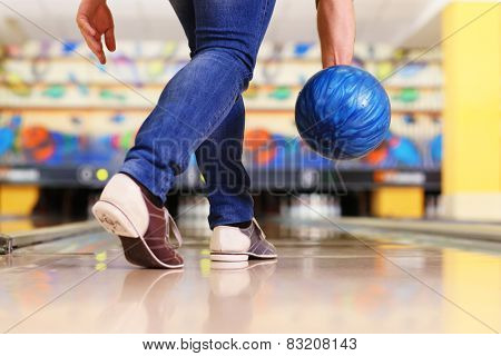 Male legs and bowling ball in alley background