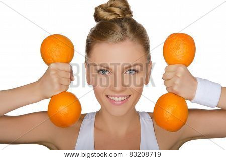 Young Woman With Dumbbells From Ripe Oranges