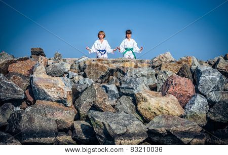 boy and girl practicing yoga on beach