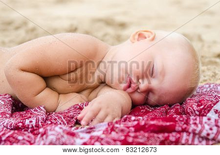 Baby sleeping on the sand