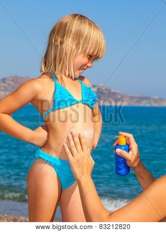 Mother applys sunblock cream to her  daughter
