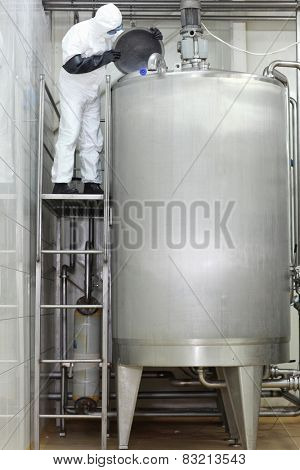 Technician in protective coveralls  controlling industrial process in factory