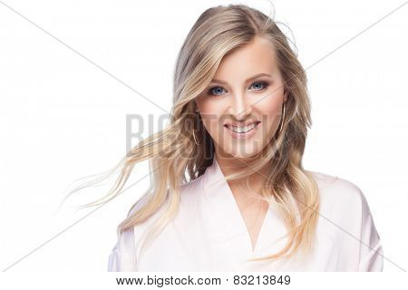 Young smiling blond lady wearing a sexy pink bathrobe isolated on white