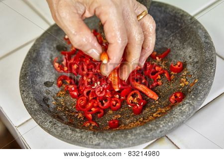 Making sambal, special chili food in Indonesia to eat together with another meal to add hot and spice flavour, all the ingredient crushed using stone pestle on stone mortar