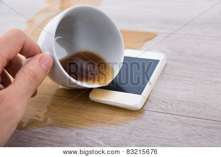 Person's Hand Spilling Coffee On Cellphone