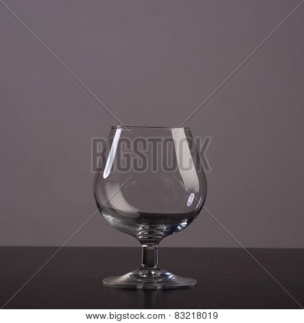 Empty cognac glass with reflections on grey background
