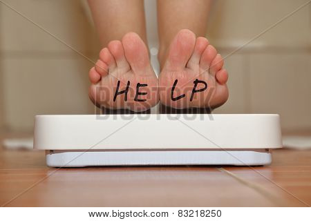 Feet on bathroom scale with hand drawn Help text