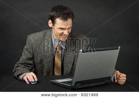 Homem furioso se senta na mesa e olha para a tela do Laptop