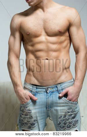 muscular man in torn jeans stands near the sofa