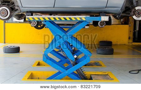 Car Under Repair On Hoist At Service Station