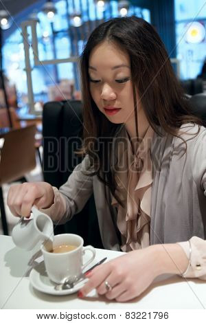 Asian girl pours cream into coffee