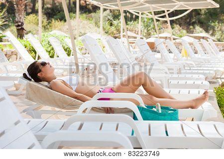 Woman In Swimwear Sunbathing On Lounge Chair