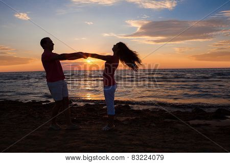 Couple Holding Hands At Beach During Sunset