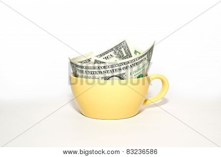 Banknotes Dollars In Yellow Cup On A White Background