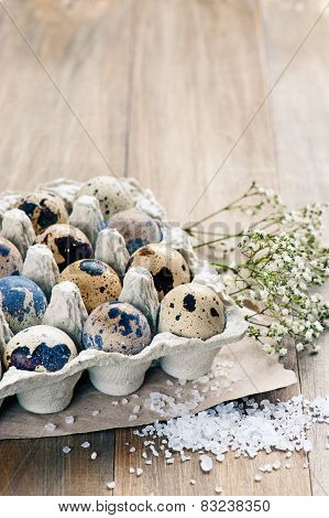 Quail Eggs In A Cardboard Packaging On A Wooden Background