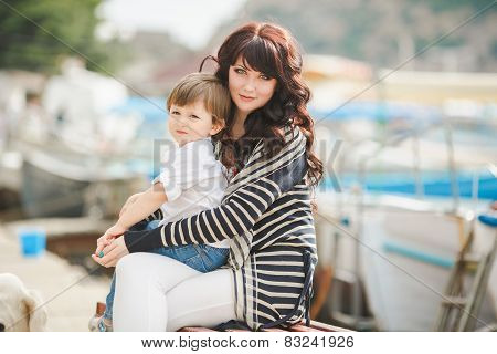 Happy mother and her young son sitting on a bench on the pier near the yacht club.