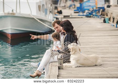 Happy family spends time on the pier near yachts.