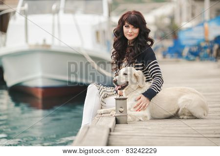 Portrait of a beautiful young woman sitting with a dog on the beach.