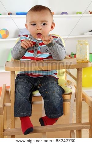 Child Eating Baby Food With Spoon