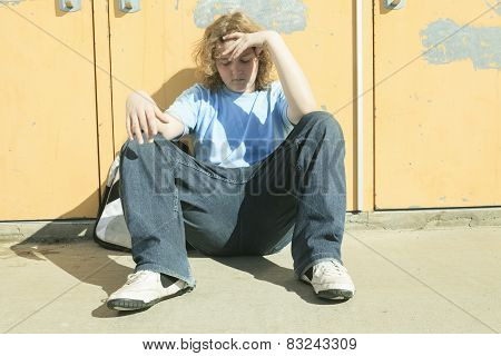 sad lonely boy in the school playground