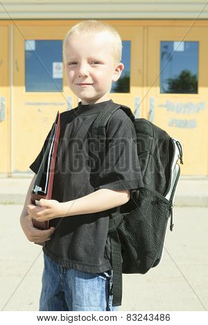 A boy on the playground of his school with a backpak