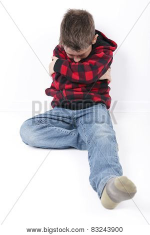 A sad young boy sit on white background