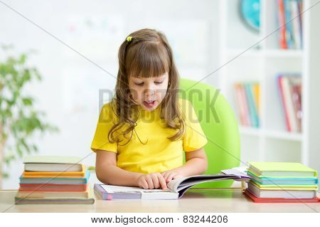 Happy child reading book at table in nursery