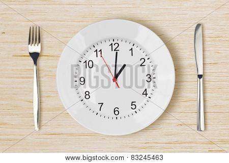 Dinner plate with clock face on wooden table