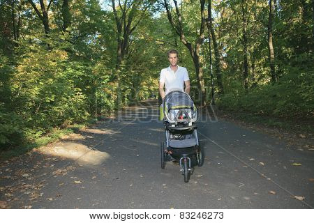 A 30 years old man with a stroller walking in the park