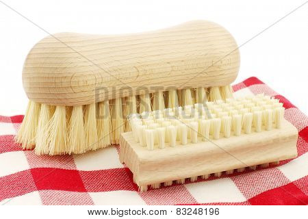 a wooden nail brush and a wooden household brush on a red and white checkered kitchen towel on a white background