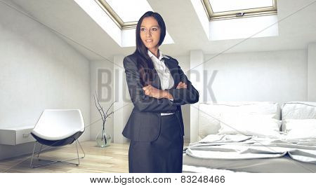 Confident Young Asian Indian Businesswoman at the White Bedroom Looking afar.
