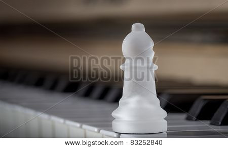 Glass chess bishop on the piano (matte)