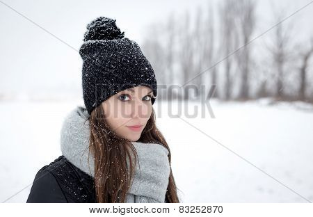 Outdoor portrait of a young girl in winter hat