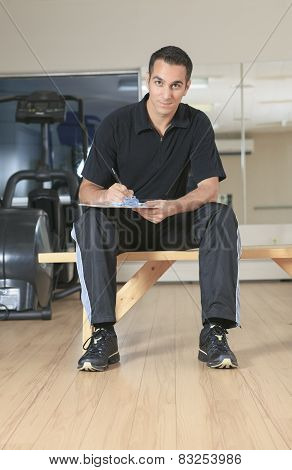 Personal trainer wearing sportswear standing with training bike,