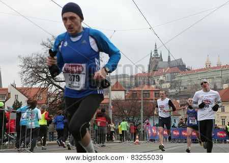 PRAGUE, CZECH REPUBLIC - APRIL 6, 2013: Athletes run in front of Prague Castle with St Vitus Cathedral during the Prague international marathon in Prague, Czech Republic.