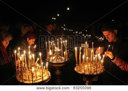 PRAGUE, CZECH REPUBLIC - MAY 5, 2013: Orthodox believers light candles during an Orthodox Easter night service in front of the Dormition Church at the Olsany Cemetery in Prague, Czech Republic.