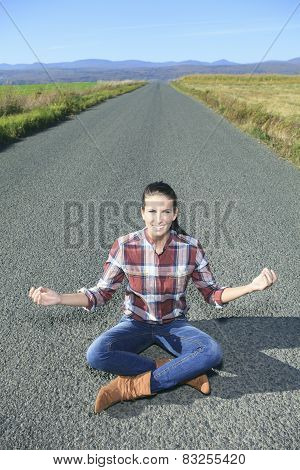 Young woman meditating in lotus position in the road